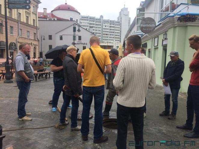 Фото дня: 10 чиновников решают, кто полезет в канализационный люк