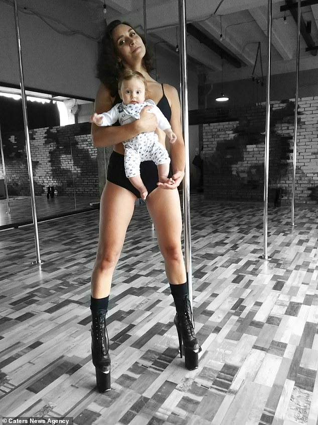 Pole dancer, 24, who continued to dance while pregnant shows off her moves while carrying her newborn baby in Belarus